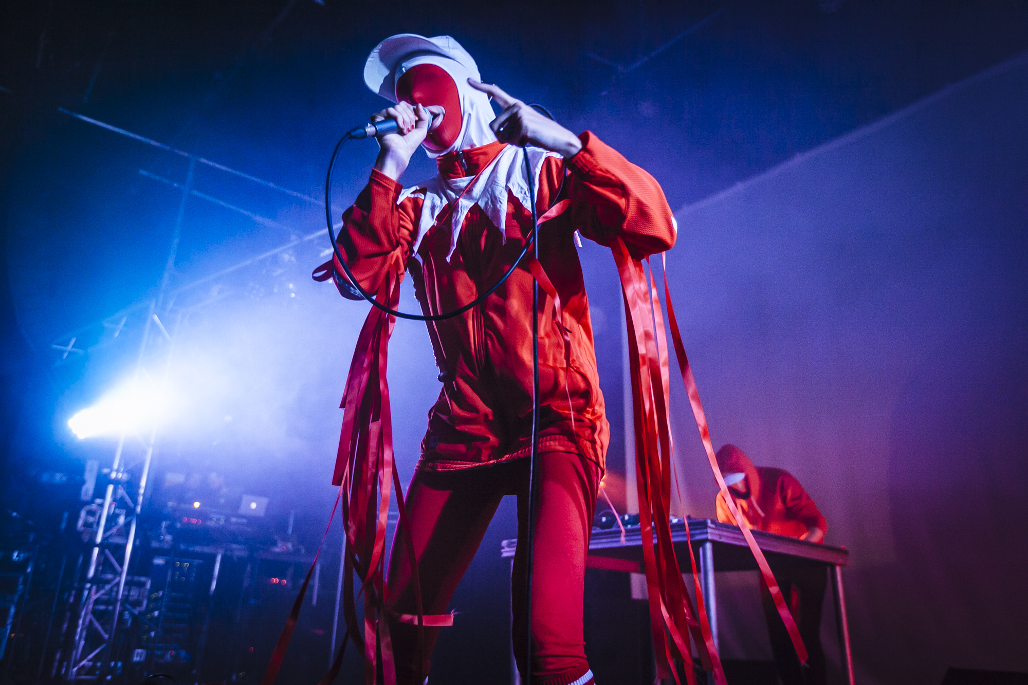 Gazelle Twin in Red Jester-style costume performing live at Supersonic 2018